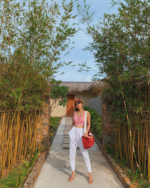 Tăng Thanh Hà khoe vòng eo săn chắc khi diện áo crop-top và quần dây rút. Phụ kiện mũ cói, túi vải thân thiện với môi trường giúp set đồ của ngọc nữ điện ảnh trở nên hoàn hảo.