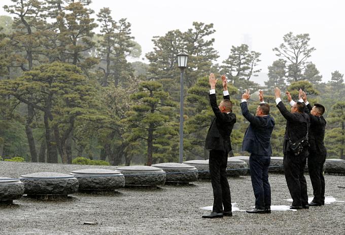 Người dân Nhật giơ tay về phía hoàng cung tại Tokyo trước lễ thoái vị của Nhật hoàng Akihito. Ảnh:AP.
