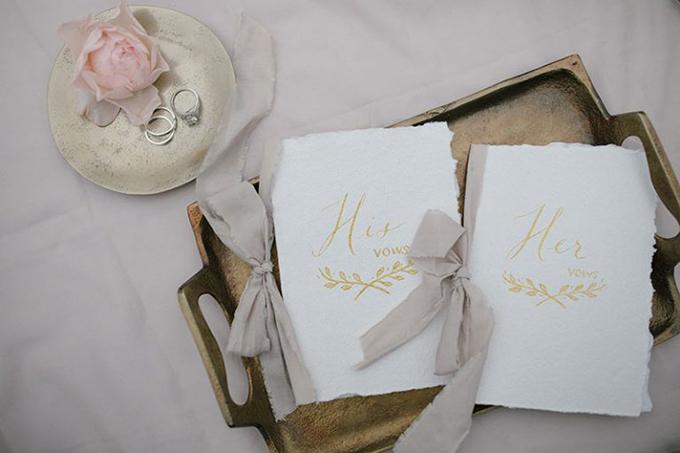 Lời thề nguyện được thắt nơ xám. Bên cạnh là bộ nhẫn cưới và nhẫn đính hôn của cả hai.