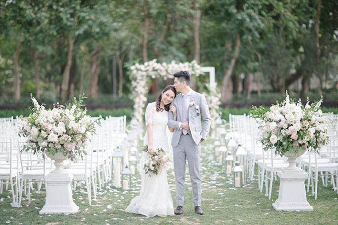 Trong khi chú rể diện bộ suit xám, cô dâu chọn bộ đầm đính ren, dáng sheath để thoải mái di chuyển trong sân vườn.