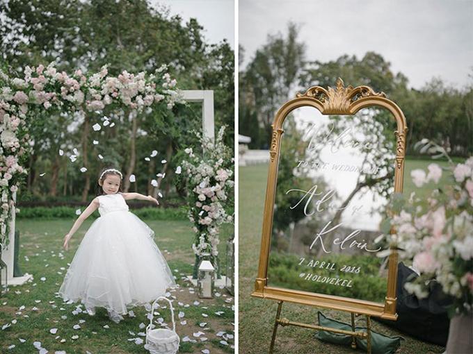 Phù dâu nhí hóa thân thành tiểu công chúa khi diện váy trắng tinh khôi, dáng xòe phồng. Bảng welcome tiệc cưới được làm từ gương và có dòng chữ thư pháp nghệ thuật bên trên theo xu hướng cưới hiện đại.