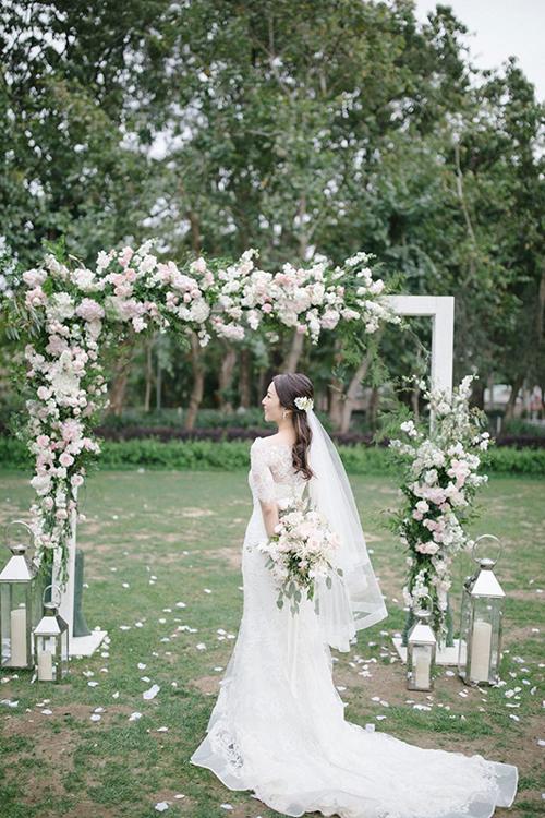 Cổng cưới mang dáng hình chữ nhật theo xu hướng trang trí cưới hiện đại. Bên cạnh là nến trắng làm tăng sự lãng mạn.
