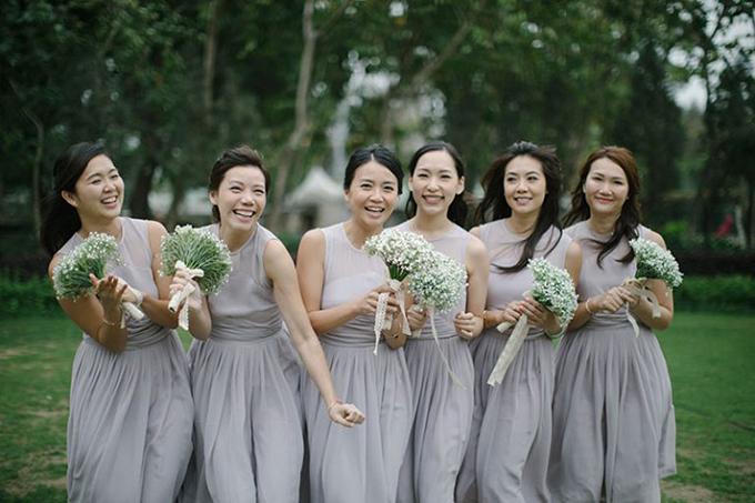 Dàn phù dâu diện váy chữ A màu xám và cầm theo hoa baby trắng.