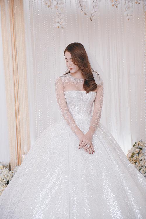 Giá trị của váy cưới là 400 triệu đồng. Bộ soiree được lên ý tưởng trong vòng 1 tháng và hoàn thiện trong vòng 30 ngày tiếp theo bởi NTK Linh Nga và đội ngũ gồm hơn 10 người. Váy có phom dáng cổ cao, cúp ngực ngang, chân váy xòe bồng bềnh hướng đến sự thanh lịch.