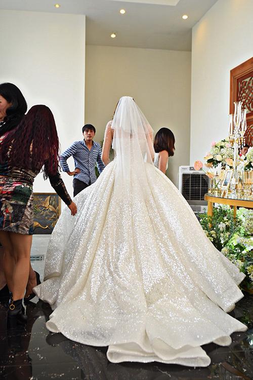 Đằng sau thân váy cũng được chú trọng, nền vải được xử lý kỹ lưỡng, tạo độ lấp lánh, giúp cô dâu nổi bật trong từng khung hình. Lê Hà diện váy kết hợp với voan cưới ngắn không họa tiết.