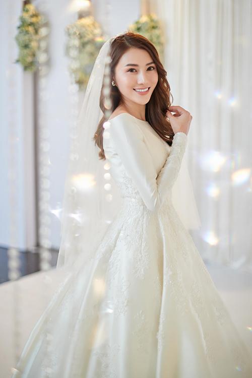 Sự mới lạ trong bộ váy tối giản cổ thuyền được thể hiện nhờ chi tiết ren và 3.000 viên pha lê Swarovski đính kết dọc thân, giúp tôn vinh nét yêu kiều của nàng dâu mới. Ảnh: Khoa Nguyễn