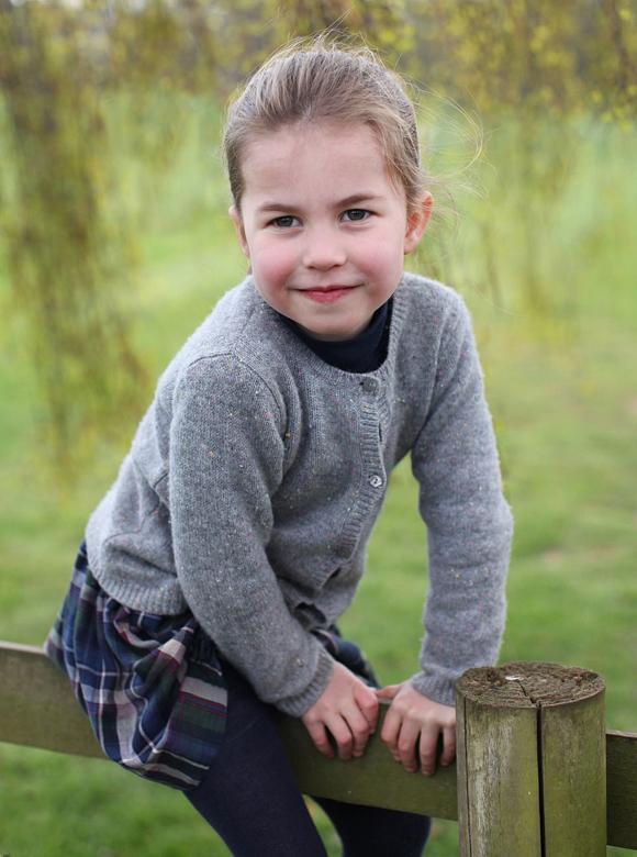Công chúa Charlotte ngồi trên hàng rào ở Anmer Hall, Norfolk hôm 15/4. Ảnh: Kate Middleton.