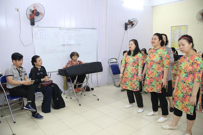 Bà ngồi một góc cùng ca sĩ Quang Thành (người quản lý) chăm chú lắng nghe người khuyết tật hát tặng mình.