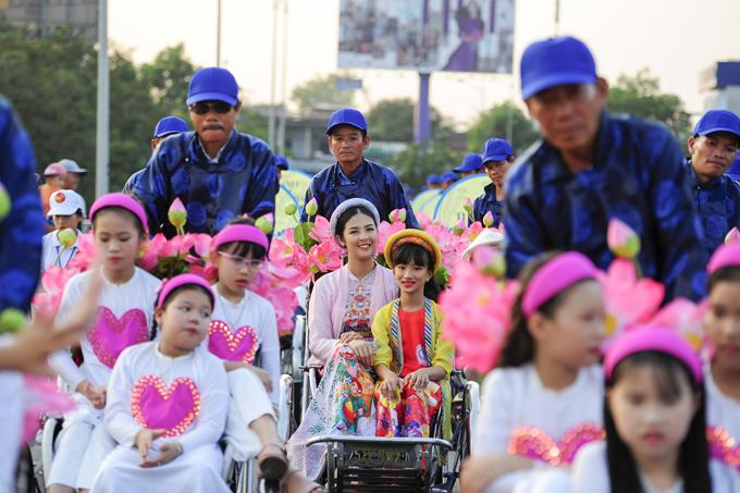Ngọc Hân ngồi xích lô cùng các em nhỏ đi diễu hành trên phố.
