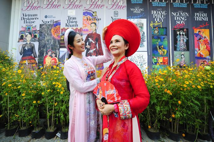 Cô chỉnh lại trang phục cho nghệ sĩ Minh Châu trong một hoạt động ở đường phố.
