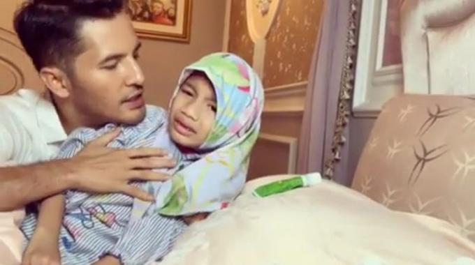 Datuk Aliff Syukri vừa bôi thuốc vừa dạy dỗ con gái 9 tuổi. Ảnh cắt từ video.