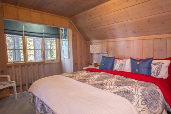 Phòng ngủ nằm ở tầng áp mái hướng ra hồ Tahoe với nột thất chủ yếu bằng gỗ đơn giản và mộc mạc.