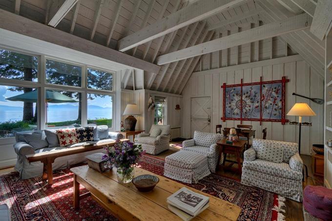 Phòng khách của căn biệt thự được thiết kế theo phong cách cổ điển với trần cao làm bằng gỗ, nội thất đơn giản và hướng mặt ra hồ.