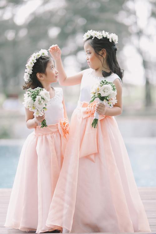 Các bé gái ăn vận điệu đà với váy chữ A mang sắc hồng và đội vòng hoa màu trắng khi làm phù dâu nhí.