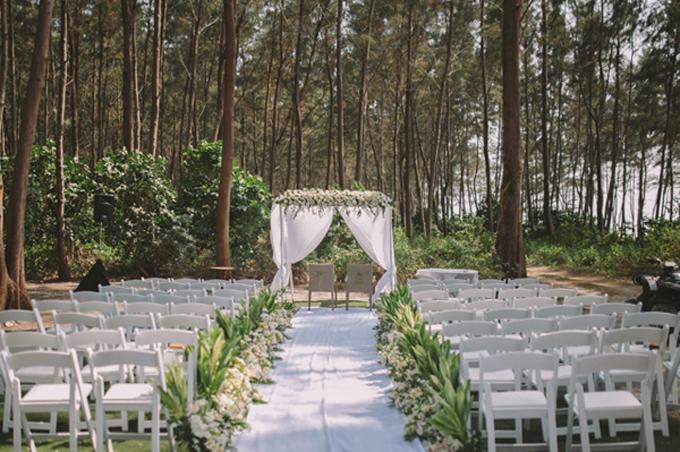 Không gian thực hiện nghi lễ cưới của cặp vợ chồng mang sắc trắng lãng mạn với ghế xếp từ gỗ. Dàn hoa hồng tươi, lá cây xanhđược xếp dọc hai bên lễ đường để tô điểm, xóa đi sự đơn điệu của sắc trắng. Phía xa là cổng cưới hình chữ nhật được kết hoa tươi.