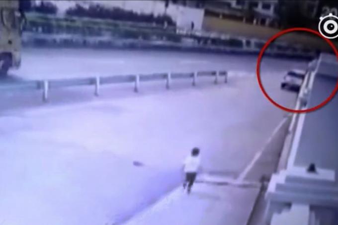 Cậu bé ra sức chạy theo xe bố mẹ khi phát hiện mình bị bỏ quên ở trạm bảo dưỡng xe. Ảnh: Weibo.