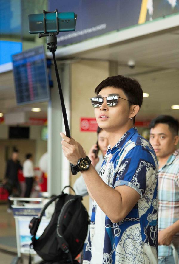 Jun Phạm khoe mái tóc mới và liên tục dùng gậy selfie lưu lại khoảnh khắc ở sân bay.