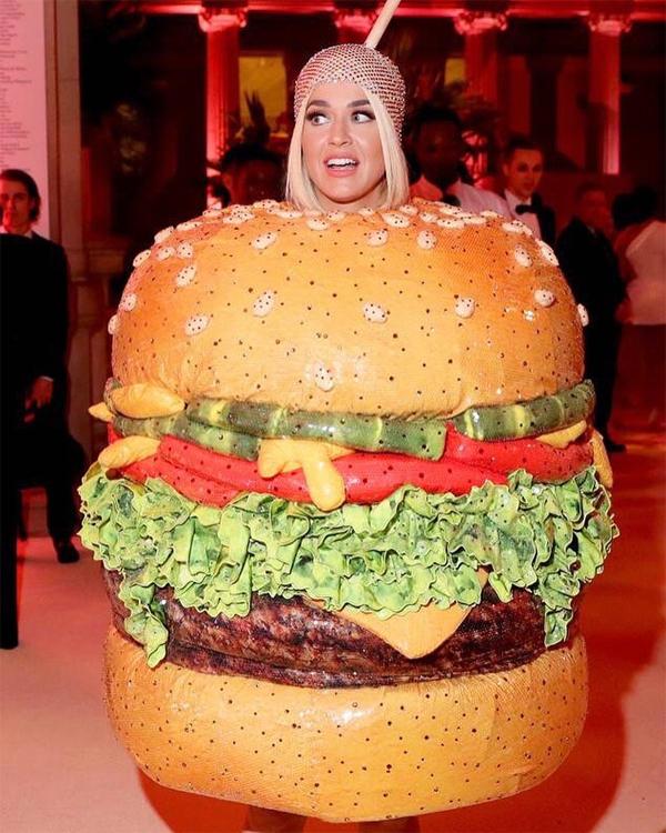 Sau khi đến thảm đỏ Met Gala với bộ váy đèn chùm rực sáng, Katy Perry thay trang phục khác cũng ấn tượng không kém, nhưng mang tính phồn thực hơn tính thời trang. Cô khoác lên người mô hình chiếc bánh hamburger khổng lồ, ngồn ngộn rau và thịt.