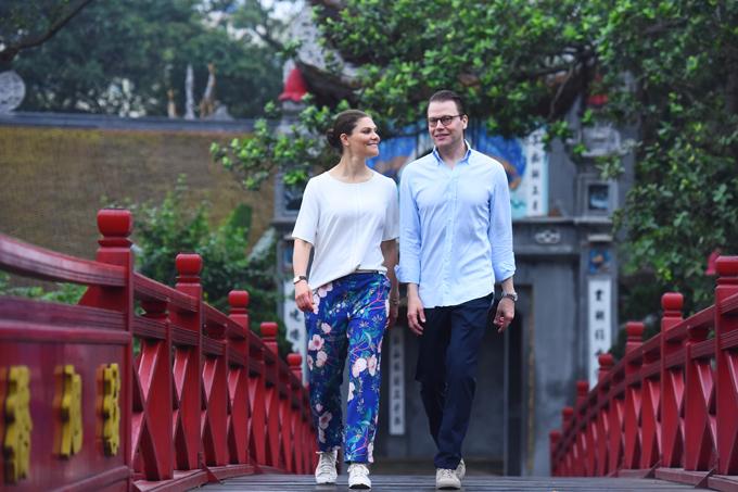 Công chúa Thụy Điển đi giày thể thao trắng, ăn mặc giản dị với áo phông trắng và quần dài hoa, sánh vai phu quân đi dạo trên cầu Thê Húc sau khi thăm đền Ngọc Sơn.