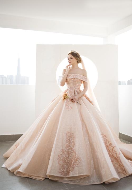 5. Váy cưới xòe phồng ánh kimMẫu đầm tiếp theo cũng gợi tả vẻ đẹp ánh hoàng hôn với sắc hồng - cam dịu mắt. Chất liệu kiến tạo nên thiết kế này là vải organza phủ kim tuyến.