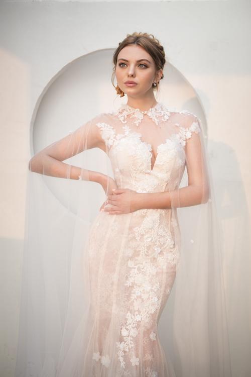 6. Váy đuôi cá đính hoa 3DMẫu váy được kết hoa 3D với áo choàng voan mỏngdễ dàng chiếm trọncảm tình của nàng dâu. Bộ đầm giúp tôn sắc vóc gợi cảm của nàng với các đường cắt cúp ôm sát. Thiết kế được bán với giá 22 triệu đồng, giá thuê là 9 triệu đồng.