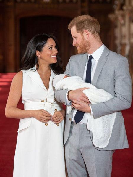 Meghan mặc chiếc váy trắng của Givenchy thắt đai dưới ngực, để lộ bụng to sau sinh. Ảnh: PA.