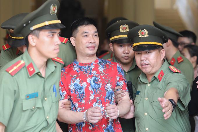 Dương hơi khựng lại khi gặp bố, ông Văn Kính Thái, bên ngoài phòng xét xử lúcđược dẫn giải ra ngoài sau phiên tòa sáng nay, 8/5. Ảnh: Thành Nguyễn.