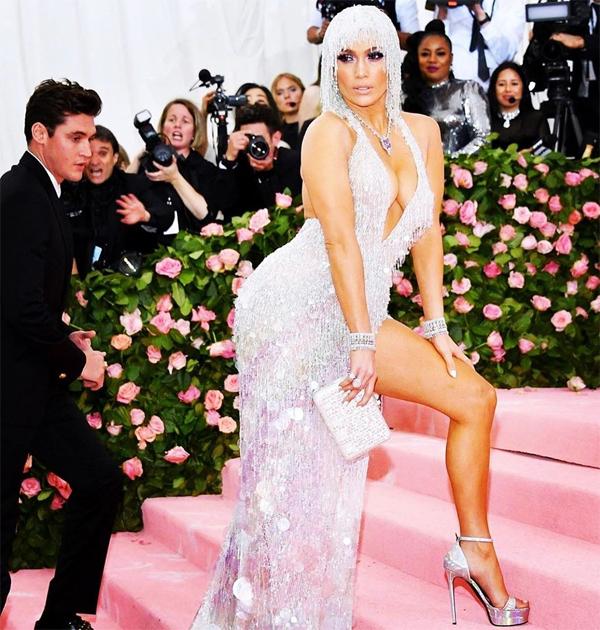 J.Lo mặc bộ đầm gợi cảm của Versace, khoe đường cong bốc lửa. Một chàng trai trẻ đi ngang qua cũng không thể rời mắt khỏi cô.