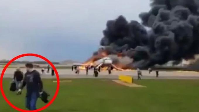 Nhiều hành khách cố cứu hành lý khi thoát ra khỏi chiếc Sukhoi Superjet 100 hôm 5/5. Ảnh: News.com.au.