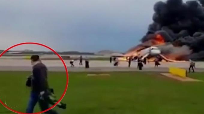Một trong số những hành khách cầm hành lý xách tay ra khỏi chiếc máy bay bốc cháy ở Nga hôm 5/5. Ảnh: Ren TV.