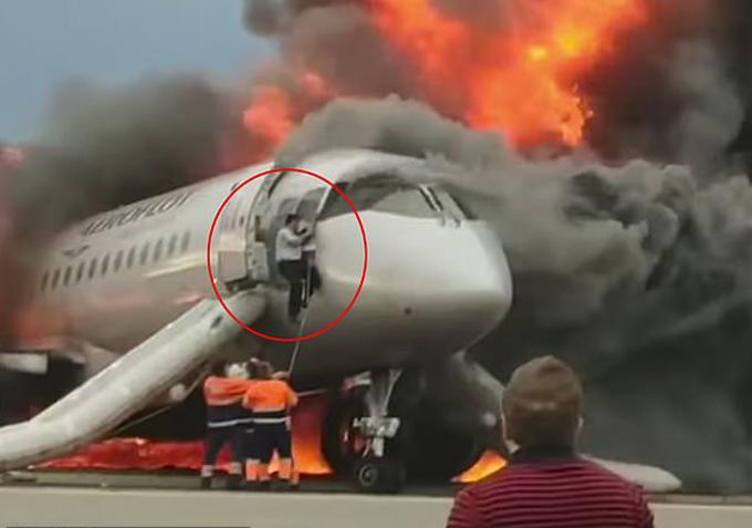 Cơ phó Maxm Kuznetsov trèo khỏi cabin đầy khói sau khi máy bay bốc cháy ở sân bay Sheremetyevo hôm 5/5. Ảnh: Ren TV.