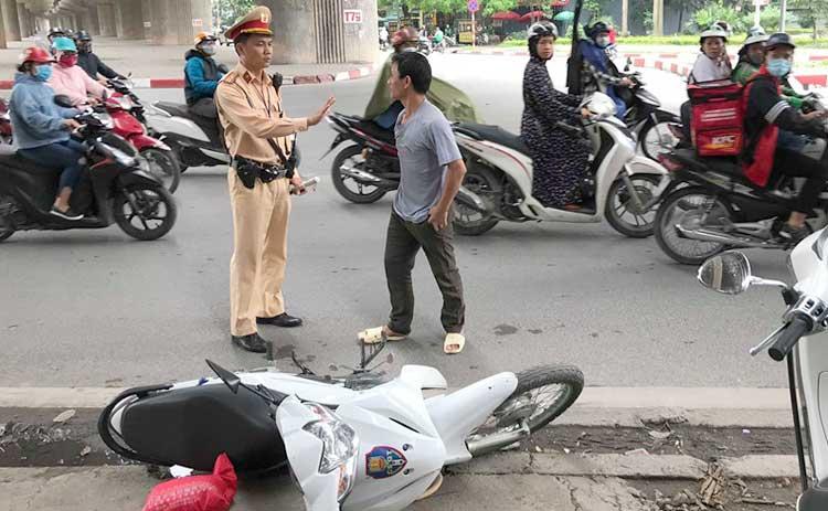 Người đàn ông ngồi sau xe máy sau khi đạp đổ xe máy của tổ công tác đãlao vào tấn công ảnh sát. Ảnh: Phương Sơn