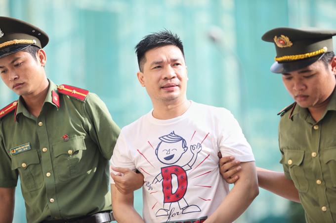 Văn Kính Dương đến tòa trong chiếc áo phông trắng in họa tiết chữ D. Ảnh: Thành Nguyễn.