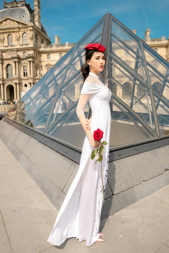 Áo dài trắng được biến tấu ấn tượng bởi phần vai trễ lấy cảm hứng từ những mẫu váy dạ hội lộng lẫy. Bên cạnh đó, mũ công nương cũng được sử dụng để tăng sức hút cho bộ trang phục.