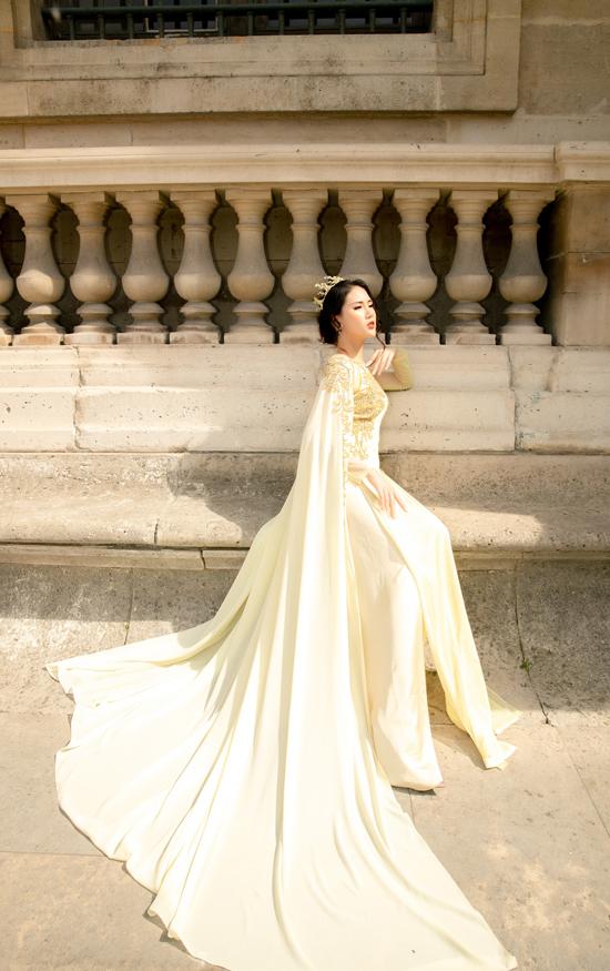 Áo dài lụa vàng được thêm phần vai choàng ảnh hưởng từ phong cách áo cape. Trang phục phù hợp với những buổi dạ tiệc hoành tráng hay dành cho các thí sinh tham gia các cuộc thi sắc đẹp tầm cỡ.