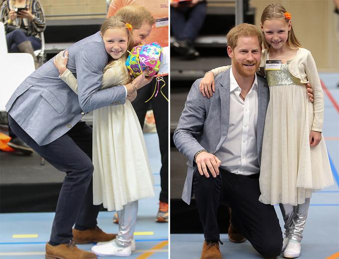 Công tước xứ Sussex ôm bé Daimy Gommers và cảm ơn vì món quà của cô bé dành cho con trai của mình. Ảnh: PA.