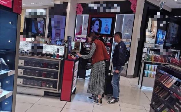Vợ chồng Lý GIa Hân chọn đồ ở cửa hàng miễn thuế tại sân bay.