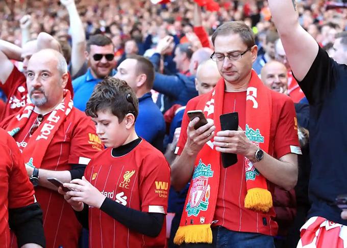 Các fan Liverpool vừa cổ vũ đội nhàvừa cập nhật tỷ số trận đấu giữa Man City và Brighton qua điện thoại.