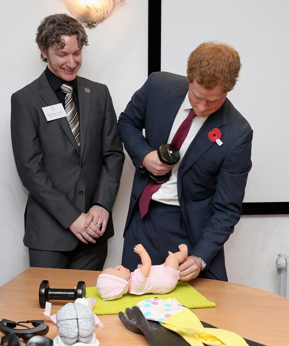 Harry từng học cách thay tã bằng một tay cho búp bê em bé trong chuyến thăm chính thức Hiệp hội chăm sóc những người tổn thương não ởNottingham vào năm 2013, trước khi vợ chồng anh trai đón chào con đầu lòng. Ảnh: Chris Jackson.