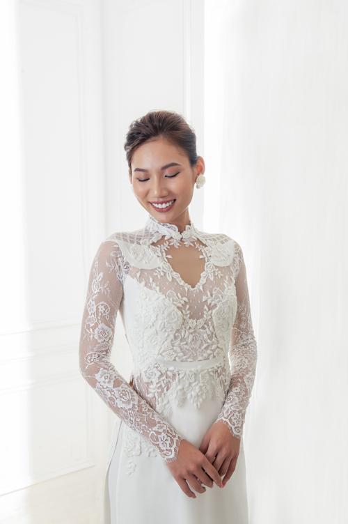 Cổ áo được thiết kế với khoảng hở hình trái tim. Thân áo được trang trí cầu kỳ với đường viền ren, giúp vẻ ngoài của cô dâu thêm nhẹ nhàng, mềm mại. Phần ngực và tay áo được táp vải có độ xuyên thấu, gợi cảm.