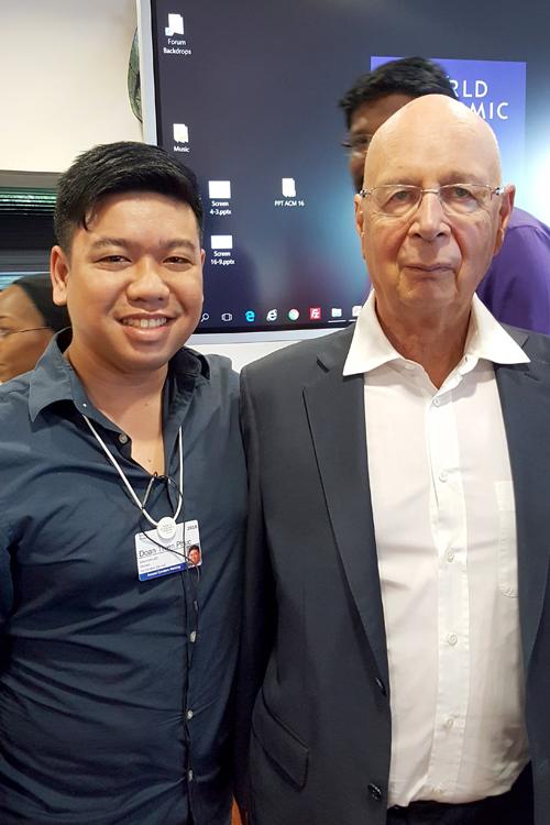 Chú rể Thiên Phúc chụp ảnh bên Giáo sư Klaus Schawbtại Diễn đàn Kinh tế Thế giới.