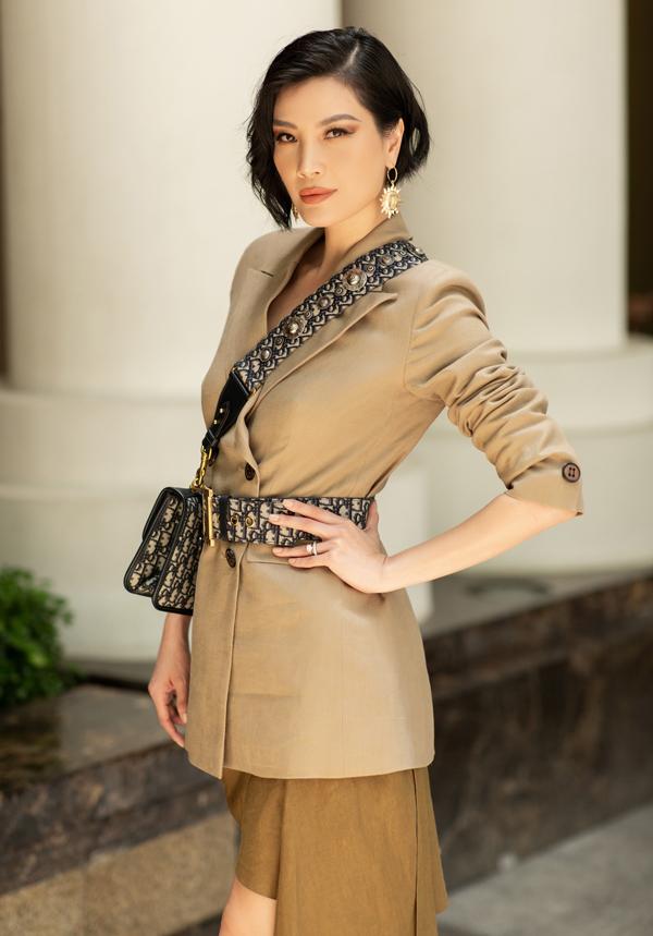 [Caption] Cựu siêu mẫu Vũ Cẩm Nhung phối áo vest dáng dài cùng chân váy linen ngắn trên gối vừa tạo nên sự thanh lịch nhưng cũng không kém phần gợi cảm. Hai tông màu đậm, nhạt được kết hợp cùng nhau tạo nên một tổng thể hoàn hảo. Cựu siêu mẫu phối trang phục cùng thắt lưng to bản, túi xách đồng điệu hoạ tiết trẻ trung của Dior.