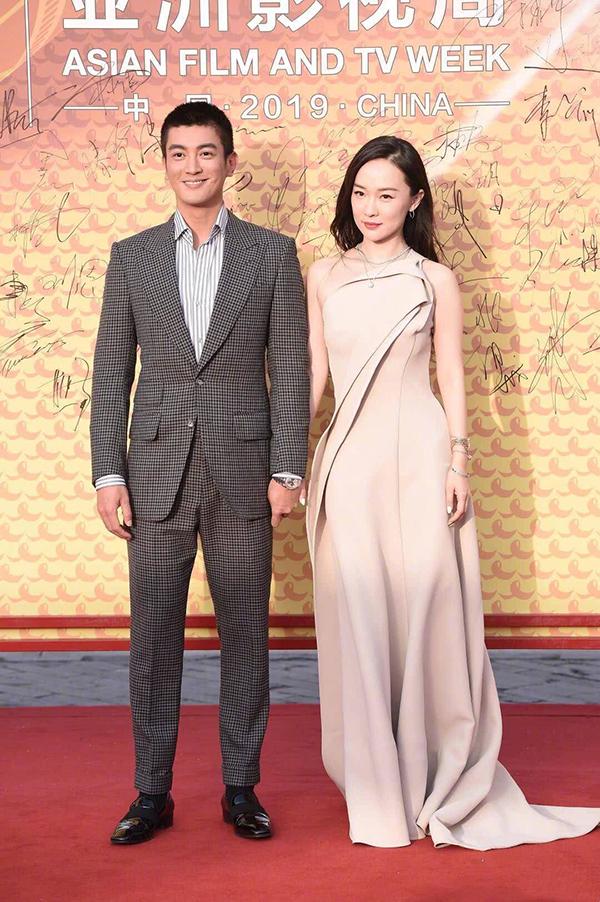 Nữ diễn viên Hoắc Tư Yến mặcváy lệch vai trang nhã, nắm tay chồng đi thảm đỏ.