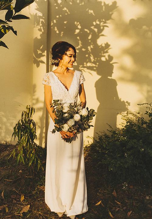 Cô dâu diện váy cưới mang phom dáng chữ A đính ren ở thân trên và có cổ chữ V xẻ ngực gợi cảm.