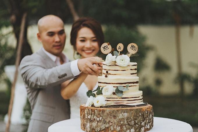 Bánh cưới của uyên ương được đặt trên thớ gỗ và mang tông màu trắng pha nâu nhạt.