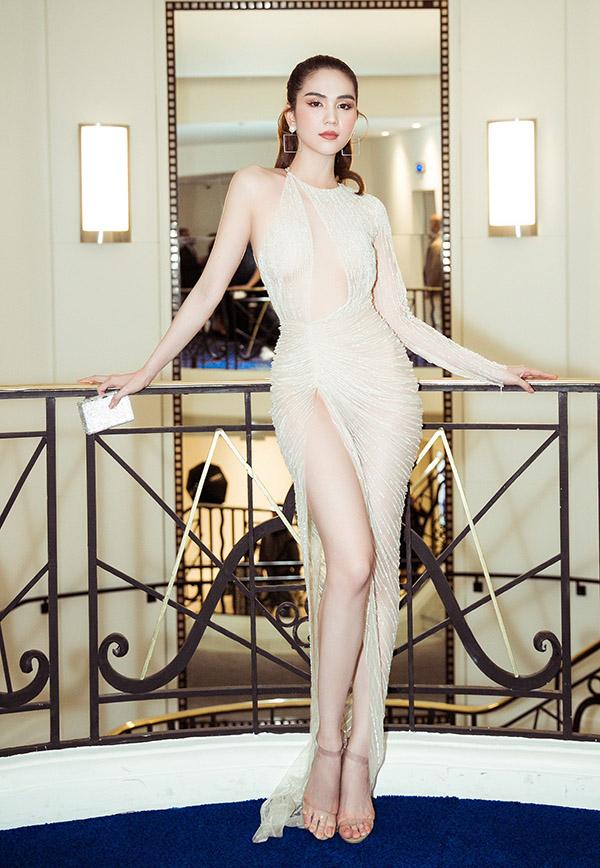 [CaptionDiện bộ đầm sexy của nhà TK Lê Thanh Hoà Ngọc Trinh khoe trọn vóc dáng trứ danh đồng hồ cát của mình, cô nhận được nhiều lời khen ngay cả đứng chung với thiên thần Victoria Secret Taylor_ Hill ( mặc đầm trắng ) . Đây là lần đầu tiên Ngọc Trinh tới Cannes và cô rất hào hứng,