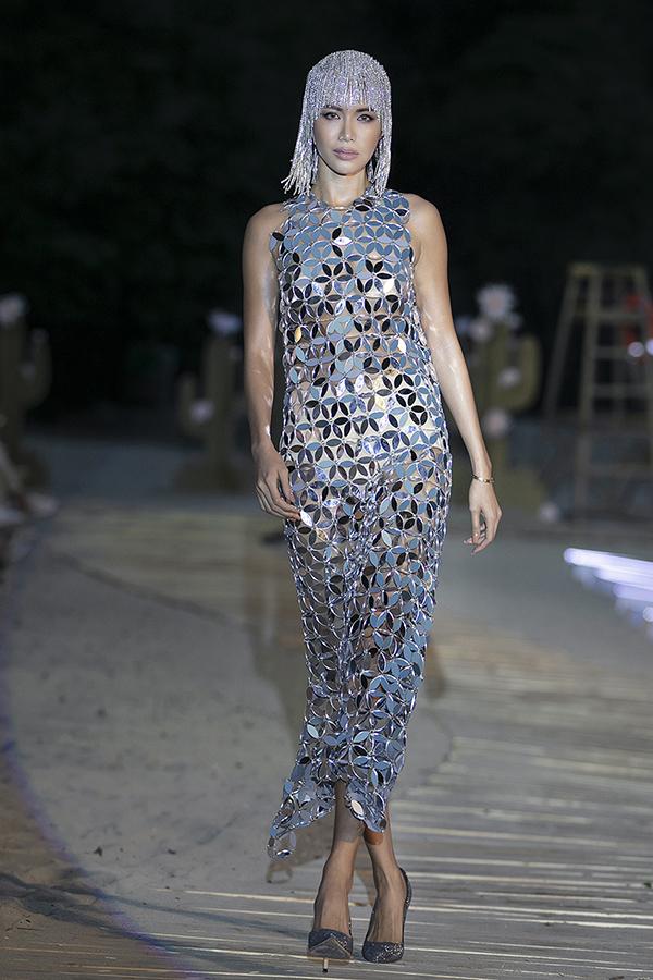 Hà Nhật Tiến giao vị trí vedette cho người mẫu Minh Tú. Cô diện thiết kế váy bó sát màu ánh bạc, kết hợp phụ kiện đội đầu bắt mắt.