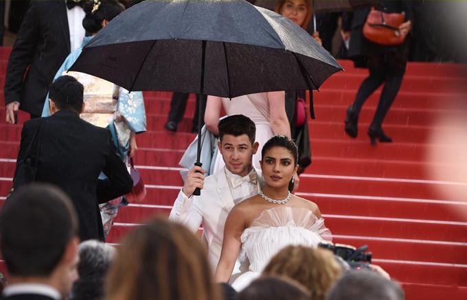 Vợ chồng Priyanka nán lại chụp hình dưới mưa.