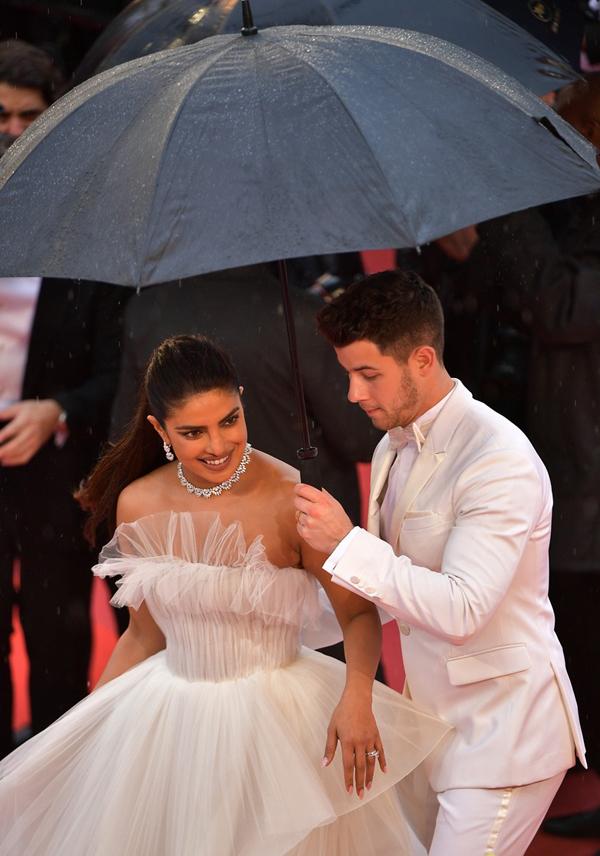 Một cơn mưa bất chợt đổ xuống giữa lúc vợ chồng Priyanka đang tạo dáng chụp hình. Ban tổ chức đã đưa cho cặp sao chiếc ô để che mưa.
