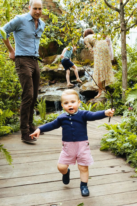 In the background, George - dressed in a short-sleeve top and blue shorts - shows off his adventurous side as he climbs a rock waterfall next to mum Kate, who is balanced on a large rock at her woodland wilderness garden.
